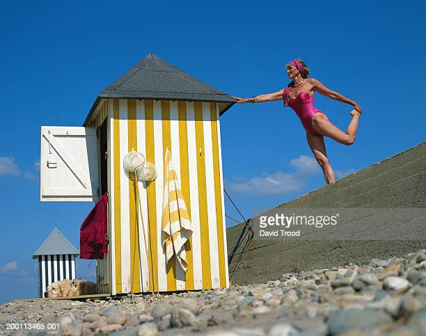 mature woman standing on one leg on wall, touching roof of beach hut - cabine de plage photos et images de collection