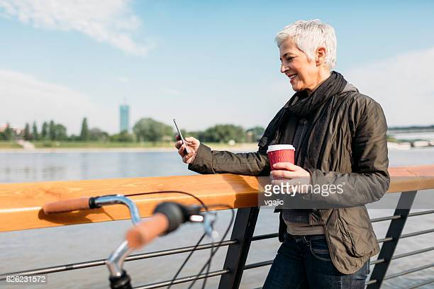 Mature Woman Standing On The Rivereside And Drinking Coffee.