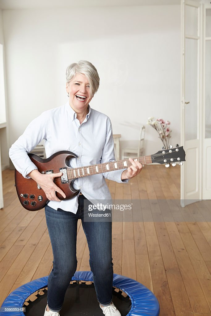 Mature Woman Standing On Trampoline Playing Electric Guitar Stock Photo