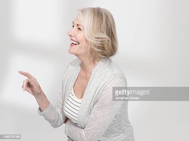 Mature woman standing pointing and laughing