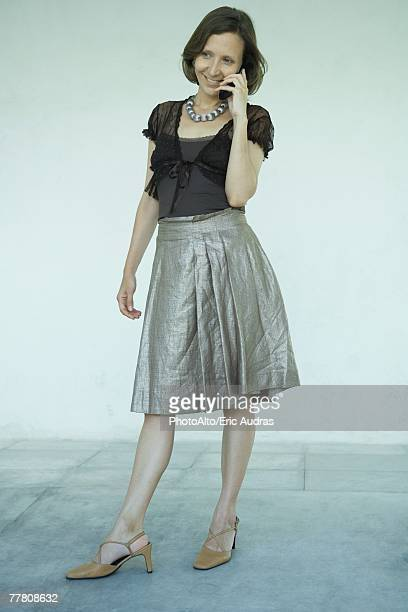 mature woman standing, using cell phone, full length portrait - silver skirt stock pictures, royalty-free photos & images