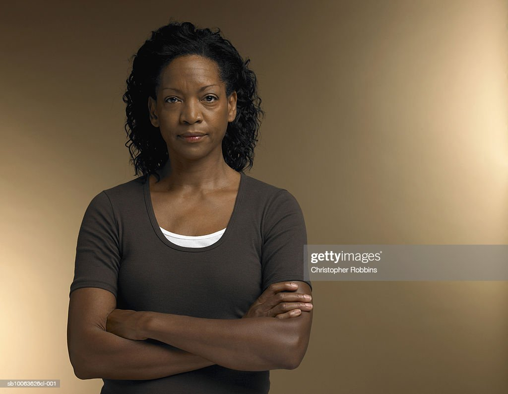 Mature woman standing with arms crossed, portrait : Stock Photo