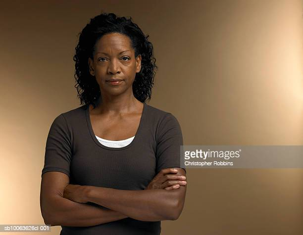 mature woman standing with arms crossed, portrait - serio fotografías e imágenes de stock