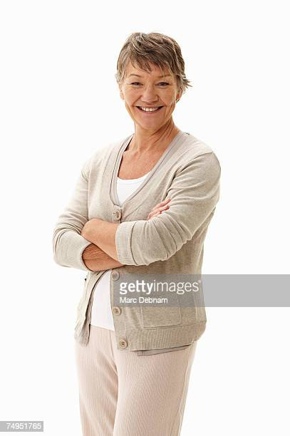 Mature woman standing with arms folded, smiling, portrait