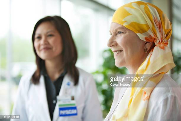 mature woman standing with doctor at hospital - chemotherapy stock pictures, royalty-free photos & images