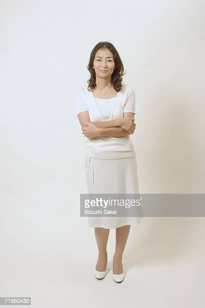 Mature woman standing with her arms crossed