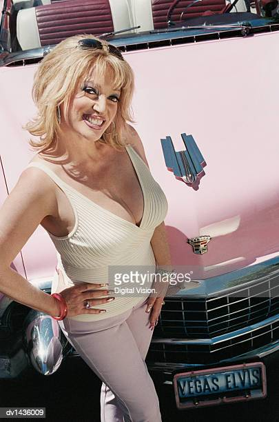 Mature Woman Standing With Her Hand on Her Hip in Front of a Vintage Car