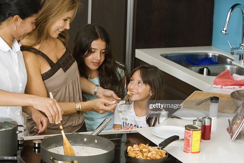 Mature woman standing with her two daughters and a maid smiling in the kitchen : Foto de stock