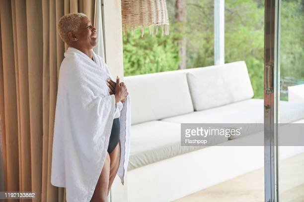 mature woman stands with a towel wrapped around her - wrapped in a towel stock pictures, royalty-free photos & images