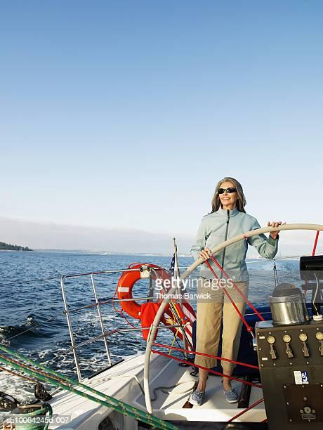 Mature woman steering sailboat, smiling