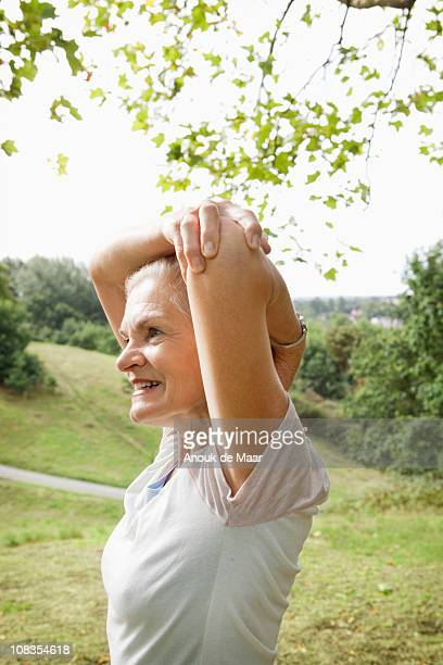 Mature woman stretches arm in park