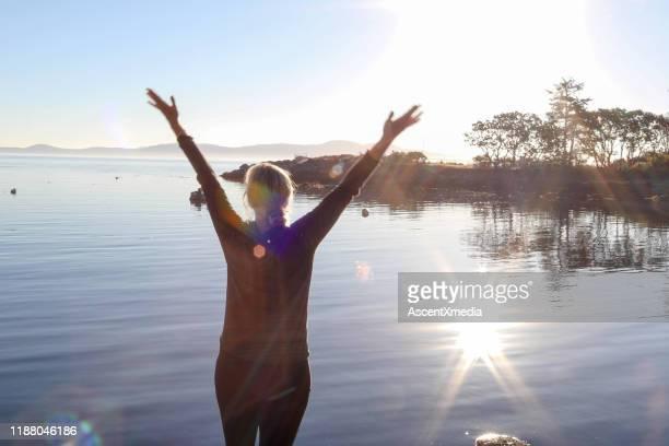 volwassen vrouw strekt zich uit aan de oever van het meer bij zonsopgang - meeroever stockfoto's en -beelden