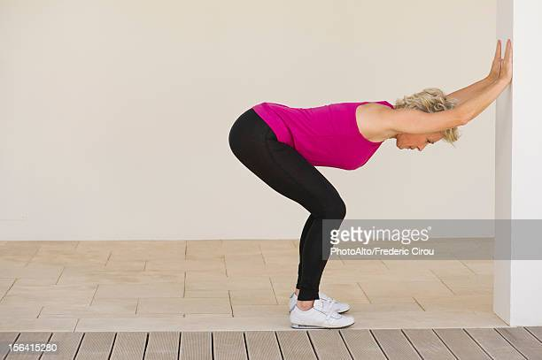 mature woman stretching against wall, side view - older woman bending over stock pictures, royalty-free photos & images