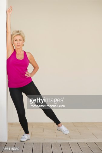 Mature Woman Stretching Arm Against Wall While Standing On -3386