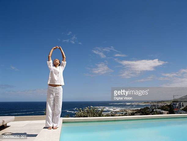 mature woman stretching by swimming pool - white pants stock pictures, royalty-free photos & images