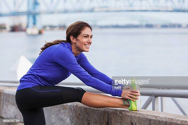 Mature woman stretching during a jog on waterfront