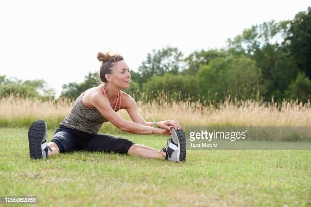 mature woman stretching in park - aktiver lebensstil stock-fotos und bilder