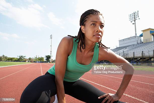 Mature woman stretching on track at track and field stadium