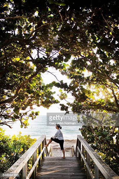 mature woman stretching on walkway, juno beach, florida, usa - juno beach florida stock pictures, royalty-free photos & images