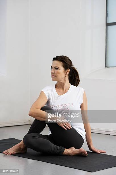 mature woman stretching on yoga mat - old women in pantyhose stock pictures, royalty-free photos & images