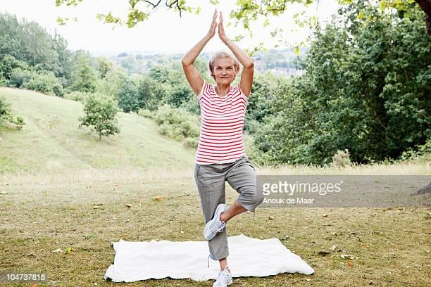 Mature woman strikes balancing pose