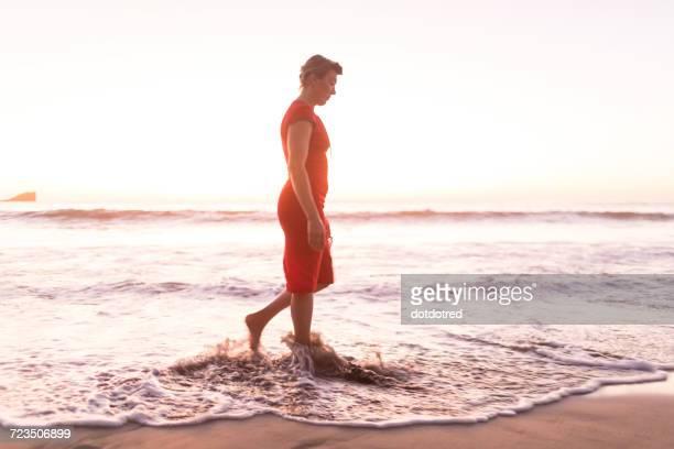 Mature woman strolling in sea at sunset, Nosara, Guanacaste Province, Costa Rica