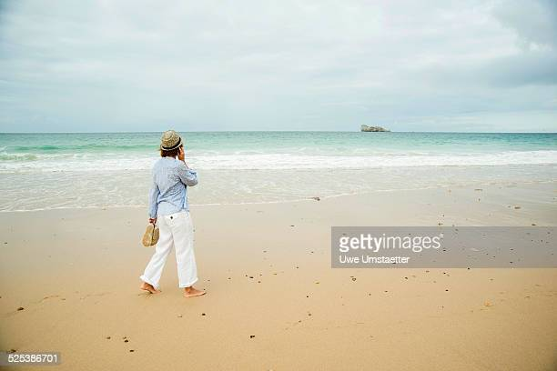 mature woman strolling on beach chatting on smartphone, camaret-sur-mer, brittany, france - white pants stock pictures, royalty-free photos & images