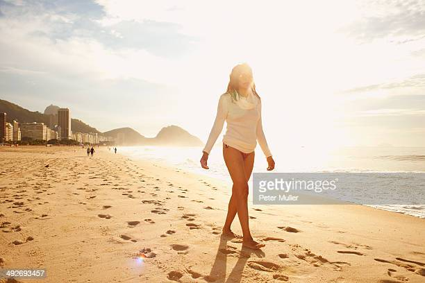 mature woman strolling on sunlit copacabana beach, rio de janeiro, brazil - indian bikini stock pictures, royalty-free photos & images