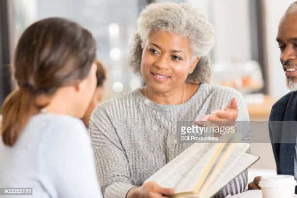 Mature woman studies the Bible with a young woman
