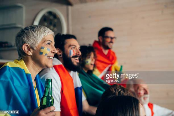 Mature woman supporting Swedish soccer team watching game with friends supporting other national teams