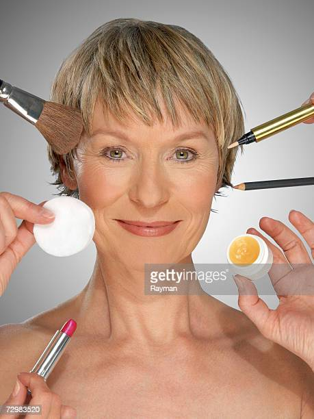 mature woman surrounded by make-up equipment, portrait - mujeres cuarentonas rubias sin ropa fotografías e imágenes de stock