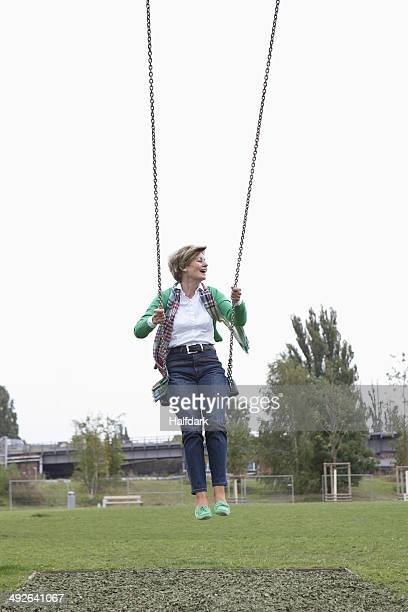 Mature woman swinging in park