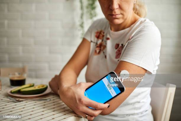 mature woman swiping sensor with smart phone for glucose mesaurement - metabolic syndrome stock pictures, royalty-free photos & images