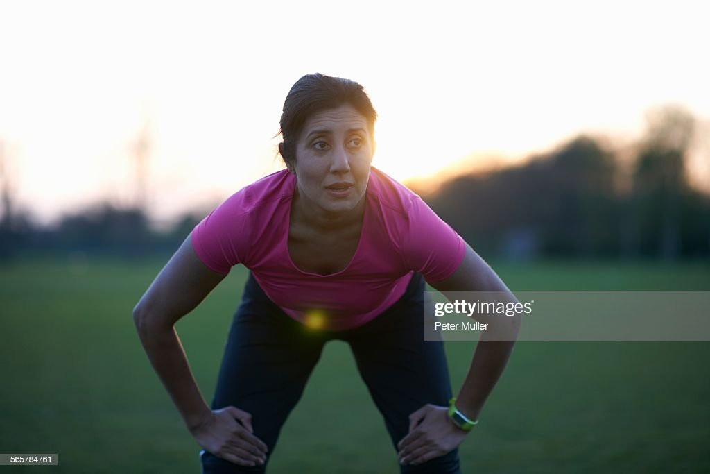 Mature woman taking a break from exercise in park : Stock Photo