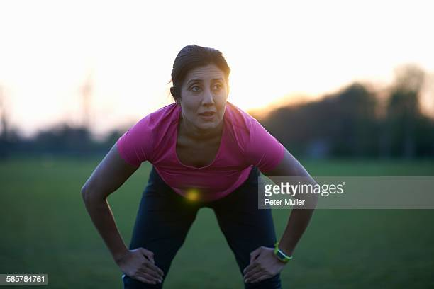 mature woman taking a break from exercise in park - older woman bending over stock pictures, royalty-free photos & images
