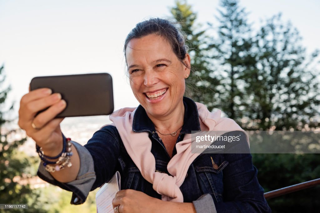 Mature woman taking a selfie in front of cityscape. : Stock Photo