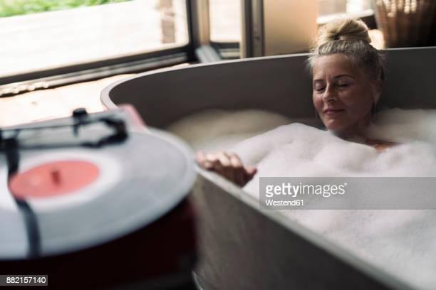 mature woman taking bubble bath, listening music from analogue record player - verwöhnen stock-fotos und bilder