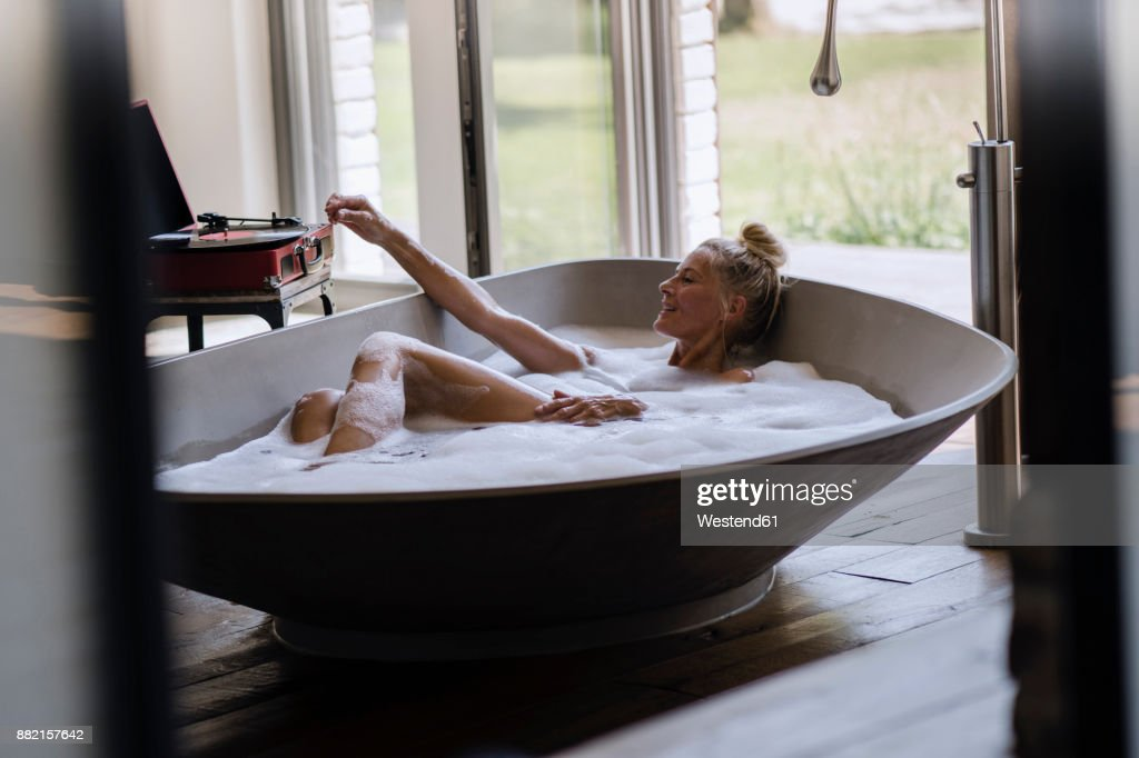 Mature woman taking bubble bath, listening music from analogue record player : Stock Photo