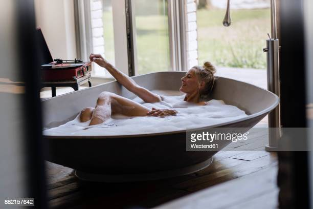 mature woman taking bubble bath, listening music from analogue record player - taking a bath stock pictures, royalty-free photos & images