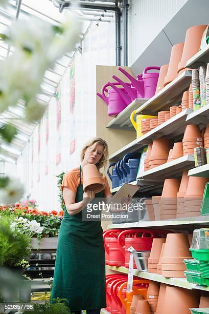 Mature woman taking inventory in garden centre, Augsburg, Bavaria, Germany