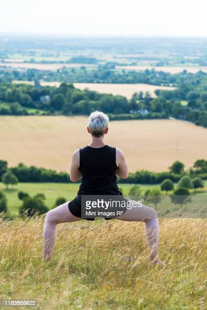 mature woman taking part in a yoga class on a hillside. - legs apart stock pictures, royalty-free photos & images