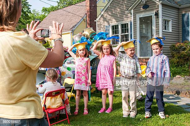 Mature woman taking photograph of children at kindergarten graduation