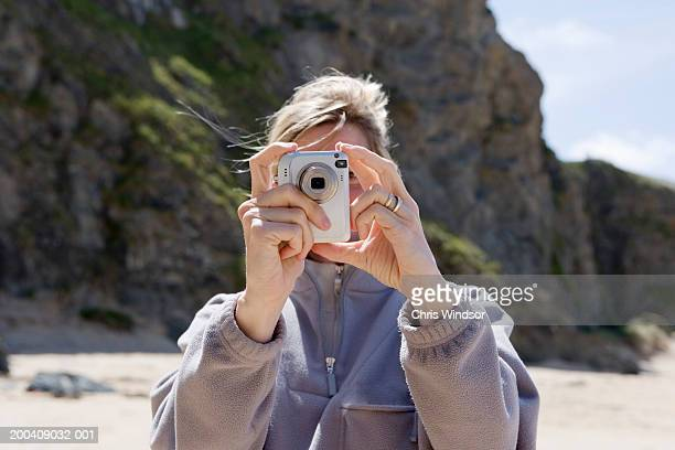 Mature woman taking photograph with digital camera, close-up