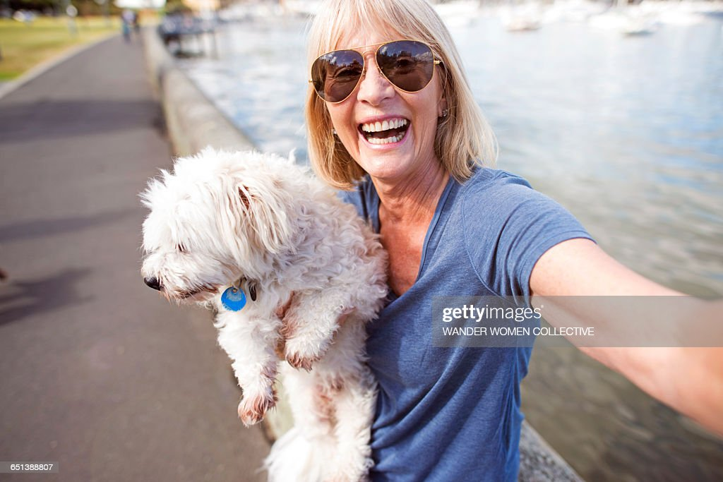 Mature woman taking selfie with dog : Stock Photo