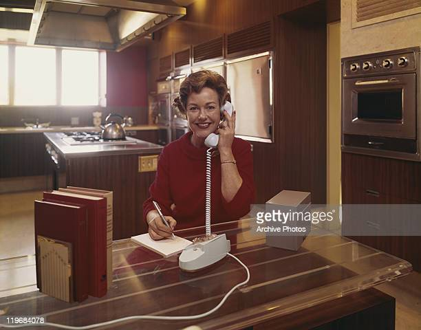 Mature woman taking telephone order, smiling, portrait