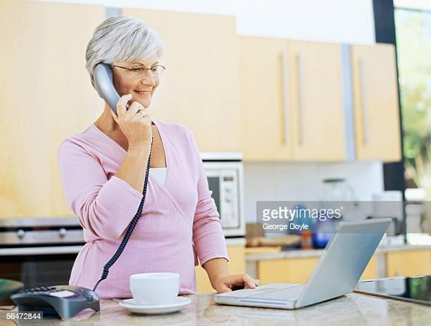 mature woman talking on a landline phone