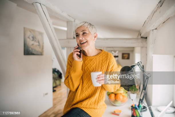 mature woman talking on phone - working seniors stock pictures, royalty-free photos & images