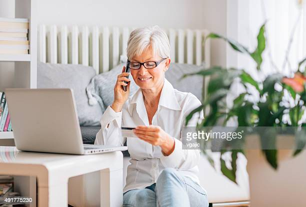 Mature Woman Talking On The Phone And Holding Credit Card.