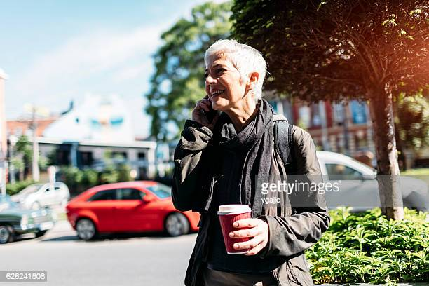 Mature Woman Talking On The Phone Outdoors.