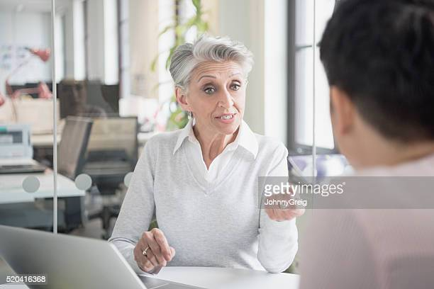 Mature woman talking to colleague in business meeting